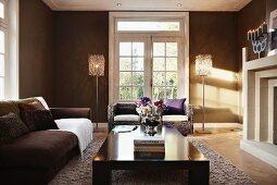Elegantes Wohnzimmer mit dunkel getönten Wänden - schwarzer Couchtisch und braunes Polstersofa, im Hintergrund Sofa zwischen Stehleuchten vor Balkon Sprossentüren