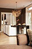 Moderne Hängeleuchte über Esstisch und weissen Polstersesseln in braun getöntem Wohnraum mit traditionellem Flair