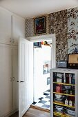 Glass-fronted cabinet against wall with strips of wallpaper in different patterns and open door leading into kitchen