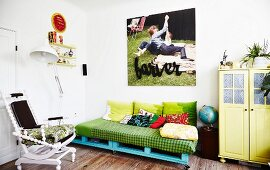 DIY sofa on blue-painted pallets, white-painted chair and yellow retro cabinet