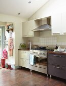 Stainless steel cooker element between light and dark base unit in simple fitted kitchen with access to garden