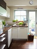 Pale and dark cabinet fronts in simple fitted kitchen with garden access