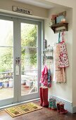 Children's coat rack with colourful aprons and wellingtons next to French windows leading to garden with French vintage sign on frame
