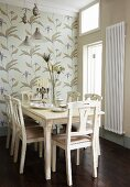 Floral wallpaper behind traditional, white, country-house-style dining set