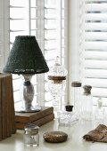 Antique glass vessels with silver lids, antiquarian books an table lamp in corner in front of windows with louvre blinds
