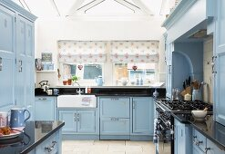 Pale blue, country-house kitchen with counter below windows with patterned Roman blinds