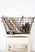 Vintage wire basket on stool used to store various objects