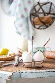 Eier in Eierständer aus Metall auf rustikalem Küchentisch