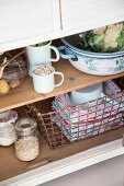 Various groceries & vintage wire basket of towels in kitchen dresser