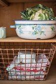 Cauliflower in enamel bowl & wire basket of towels on dresser
