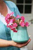 Pink phlox flowers in vintage, turquoise teapot held in woman's hands
