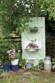 Planted, vintage washstand against mint-green board door in garden