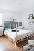 Double bed with white metal frame and dog in dog basket in rustic bedroom