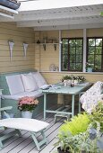 Bench and table in yellow loggia with white wooden floor