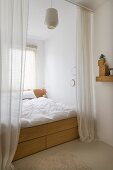 Floor-length open curtains screening double bed with drawers in wooden frame built into window niche