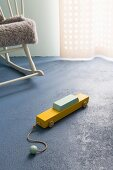 Painted wooden toy car on blue concrete floor