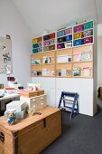 Storage boxes on top of wooden trunk and colourful baskets on partition shelving in study