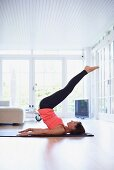 Woman performing exercises on yoga mat in living room