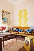 Yellow and wooden 70s retro furniture, yellow painting on wall above sofa with blue-patterned cushion