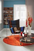 A classic wing chair and a mobile side table on a round, red felt rug in a modern setting