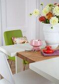 Dahlienstrauss in weisser Vase auf Tisch aus drei geteilten Platten, teilweise sichtbarer grüner Stuhl