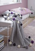 A winter throw decorated with coloured pom-poms on a day bed with a white frame against a lilac painted wall