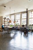 Dining table, cantilever chairs and vintage-style heating stove in loft-apartment interior with industrial glazing