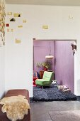 Artistic wall decoration above sheepskin blanket on bench in corner; view into living room with purple walls
