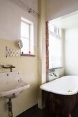 Bathroom with old bathtub and original sink in loft apartment