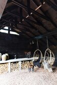 Two wicker hanging chairs with sheepskin blankets hanging from roof beam in barn with firewood stacked against wall