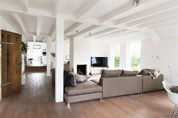 Elegant, pale grey sofa combination in open-plan interior with rustic charm, white, wood-beamed ceiling and pillars