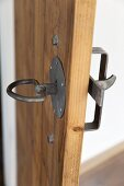 Wrought iron door latch and handle on simple, plain wooden door