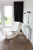 Modern, white Corian chaise in corner on wooden floor in front of dark curtains on French doors