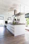 Designer island counter below extractor hood in open-plan kitchen with white, wood-beamed ceiling