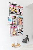 Colourful women's magazines in magazine rack, candle on slice of tree trunk and knitted soft toy
