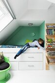 Teenager's bedroom with sloping ceiling; boy on raised bed in niche with drawers below