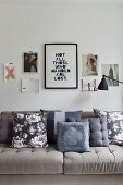 Patterned scatter cushions in shades of grey on beige sofa below collage of pictures on wall
