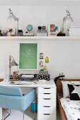 Blue, retro chair at white desk below table lamps and various objects on floating shelf in children's bedroom
