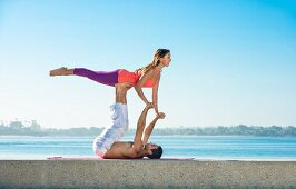 A couple in an acrobatic yoga position on the beach at San Diego