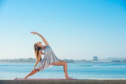 A young woman wearing a short summer dress holding an elegant yoga position on the beach