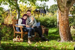 Woman and man sitting on garden bench in sunny garden with fresh apple harvest