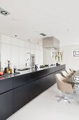 Long, free-standing kitchen with dark base units and dining set with swivel chairs