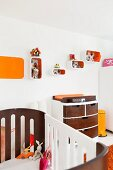 View across cot to custom chest of drawers with wooden fronts and shelving modules on wall with orange interiors