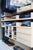 Open-fronted wardrobe with clothing hung from rail and drawers in dressing room