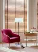 Sessel in Magenta, moderne elegante Stehleuchte und Designertischchen vor geschlossenen Holzjalousien in Fenstererker