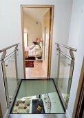 Gläserner eleganter Brückenübergang mit Blick auf unteres Geschoss und Schlafzimmer