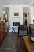 Art Deco teak sideboard and retro armchairs in open-plan interior