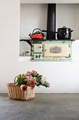 Bouquet of proteas in basket on concrete floor in front of saucepans on vintage, wood-fired cooker in niche