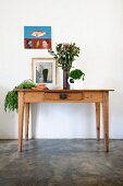 Vegetables and vase of flowers on rustic wooden table below picture on wall