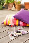 Tray of drinks, glasses and fruit tart on wooden deck with colourful cushions in background